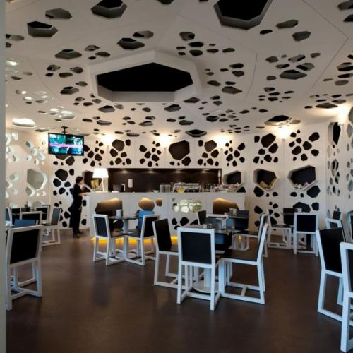 unique-concept-interior-of-a-coffee-shop-with-irregular-shapes-of-cheese-texture-in-white-color-wall-and-ceiling.jpg