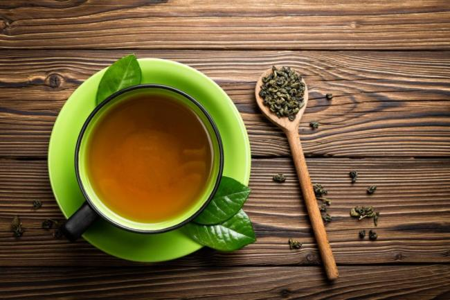 green-tea-in-cup-with-tea-leaves-on-wooden-spoon-1024x683.jpg